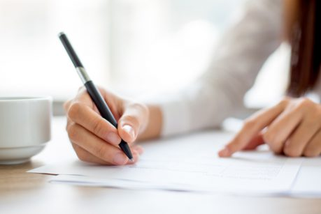 Hand,Of,Businesswoman,Writing,On,Paper,In,Office